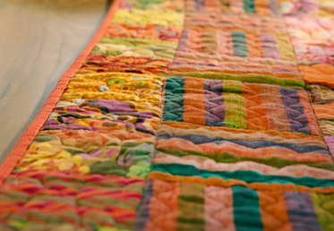 Liza Lucy deconstructs quilt construction and its vernacular – explaining patches, blocks, batting, sashing, binding, borders, quilting and more.