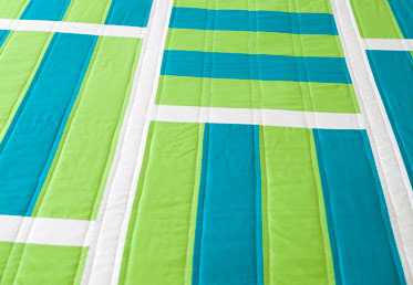In Modern Stripe Quilt Top Design - Heather Jones achieves her clean, fresh design through strip-piecing – a shortcut where you cut and sew long strips of fabric together, then cut them into blocks.