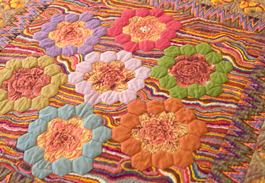 Kaffe Fassett and Liza Lucy  work together to create a masterful medallion quilt in rich, warm tones. The quilt begins with a stunning medallion center that is comprised of English paper-pieced hexagon rings and hand-appliqued fussy-cut fabrics.