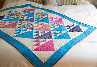 Sue Nickels and her daughter Ashley present two fun projects in their preferred styles—Sue is a traditional quilter and Ashley is a modern quilter. Though they each used the same fabrics, their finished quilts have totally different aesthetics.