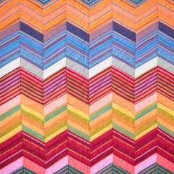 In this workshop, Kaffe Fassett talks about how to work within a rich color palette to create a light-dark zig-zag illusion, as well as how to work with solids and striped fabrics to create motifs from diamond shapes.