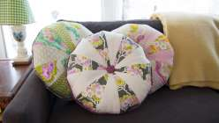 Heather Bailey teaches you how to make a fun patchwork throw pillow using fabrics from her True Colors collection with FreeSpirit. Heather teaches the front and back of this round, tufted pillow and how to make your own piping and fabric-covered buttons.