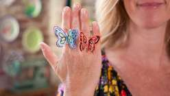 Annabel Wrigley demonstrates how to make paper butterfly rings using a Cricut Explore machine in this crafts for kids class. Learn how to decorate your butterfly shapes using watercolors, gel pens, and a felt tip marker in children's crafting lesson.